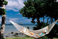 Man relaxing in a hammock in a quiet environment.
